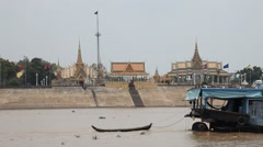 Tonle Sap river Phnom Penh palace float-by larger boat drags dingy Stock Footage