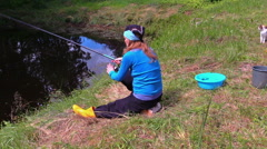 girl throw rod in pond, fishing at shore. tabby cat walk around. - stock footage