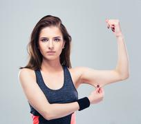 Fitness woman pinch a fat on her biceps - stock photo