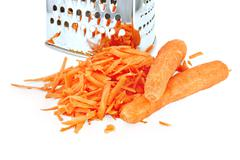 Carrots grated and whole with grater Stock Photos