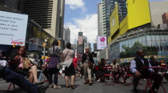 People rest at Times Square on a sunny day in New York Stock Footage