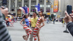 A Chinese visitor poses for a photo with two local women at Times Square Stock Footage