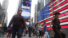 Tourisits walk past a screen showing U.S. national flag at Times Square Stock Footage