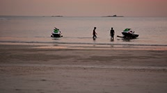 LANGKAWI, MALAYSIA - CIRCA FEB 2015: Workers hauling rental jetskis out of th Stock Footage