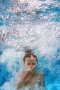 Swimming child jumps underwater in the blue pool with splashes - stock photo