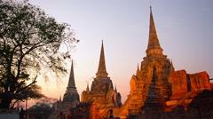AYUTTHAYA, THAILAND - CIRCA FEB 2015: Row of stupas, illuminated in shades of Stock Footage
