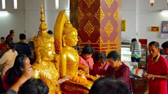 AYUTTHAYA, THAILAND - CIRCA FEB 2015: Buddhists pressing gold leaf onto statu - stock footage