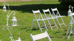 Rows of white wooden empty chairs on lawn before wedding ceremony. - stock footage