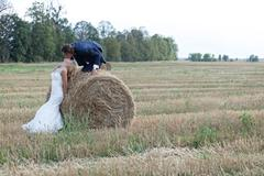 Beautiful married couple acting very romantic on a field of bales - stock photo