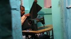 Man sewing on a sewing machine at the house entrance in Varanasi. Stock Footage