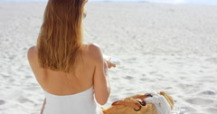 Beautiful young woman applying sunscreen to arms on beach wearing white swimsuit - stock footage