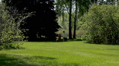 Boy runs in a green park with his pet Pekingese Stock Footage