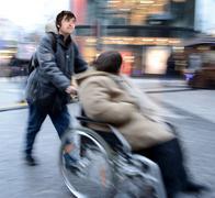 Man pushing  woman in a wheelchair - stock photo