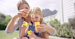 Mother and Daughter blowing bubbles in the yard happy family home Stock Footage