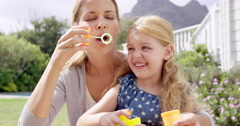 Mother and Daughter blowing bubbles in the yard happy family home - stock footage