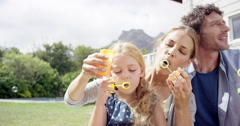 Happy family blowing bubbles in the yard at home - stock footage