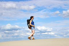 Girl with backpack hiking in desert Stock Photos