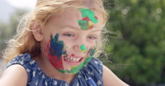 Cute preschooler learning how to paint little girls painting on face Stock Footage