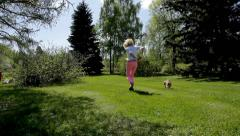 Young woman running in the park with a dog Pekingese, back view. Stock Footage