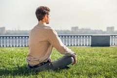 Stock Photo of Man in office suit meditate on the green lawn