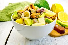 Salad seafood and avocado in bowl on light board Stock Photos
