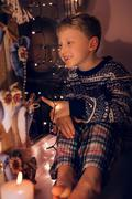 Stock Photo of Smiling little boy on the window in Christmas time