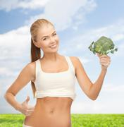 Woman pointing at her abs and holding broccoli Stock Photos