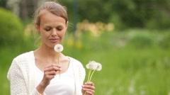 Beautiful woman blowing a dandelion Stock Footage