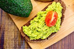Sandwich with guacamole avocado and tomato on board Stock Photos