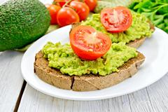 Sandwich with guacamole avocado and tomato on light board - stock photo