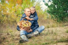 Father and son with full basket of mashrooms on the forest glade Stock Photos