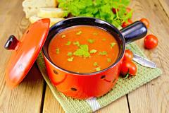 Soup tomato in red ware on board Stock Photos