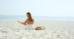 Attractive woman looking at view sitting on beach wearing one piece bathing Stock Footage