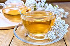 Tea with yarrow in cup on board Stock Photos