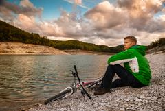 Young man cyclist relaxing near the mountain lake Stock Photos