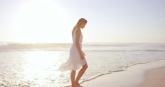 Beautiful woman wearing white dress walking on beach at sunset in slow motion - stock footage