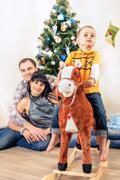 Happy family at home under christmas tree - stock photo