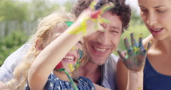 Happy family  with little girl painting in the yard creative with mom and dad Stock Footage