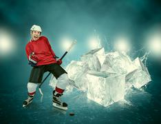 Screaming hockey player on abstract ice background - stock photo