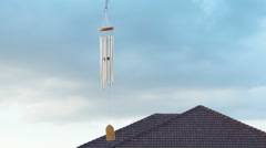 Wind chime tube mobile in breeze, Home village background. Stock Footage