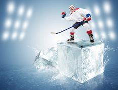 Screaming hockey player standing on the ice cube with his fist ascended - stock photo