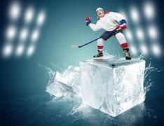 Screaming hockey player on the ice cube - stock photo