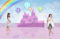 Two little girl in front of a pink fairy castle Stock Photos