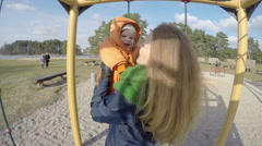 Mom and baby play on children playground outdoor sunny day. 4K Stock Footage