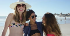 Three girl friends smiling for photograph on the beach on summer vacation Stock Footage
