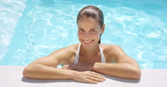 Attractive woman smiling at edge of swimming pool Stock Footage