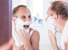 Happy man shaving in bathroom - stock photo