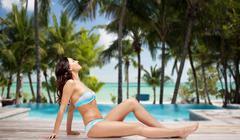 happy woman in bikini tanning over summer beach - stock photo