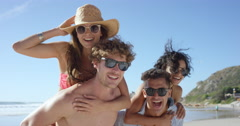 Beach couples giving piggybacks laughing having fun on vacation Stock Footage
