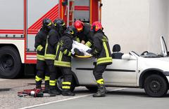 firefighters relieve an injured after car accident - stock photo
